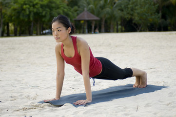A young woman performs a plank pose on tropical beach