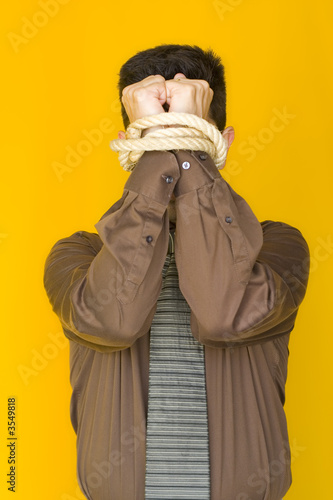 A bussinessmen tiedup by his fists with a yellow background