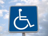 Standard disabled sign with clouds in the background poster