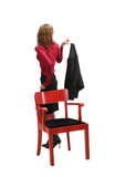 Attractive girl near red chair holding her black jacket poster