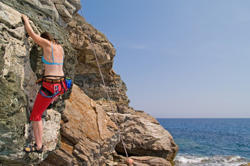 Girl climbing on the cliff