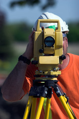 A surveyor at a construction site peering through a level
