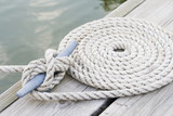Coiled mooring line tied around cleat on a wooden dock poster
