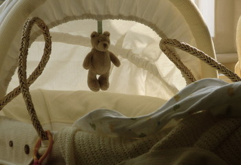 Baby cradle or moses basket with hanging teddy bear