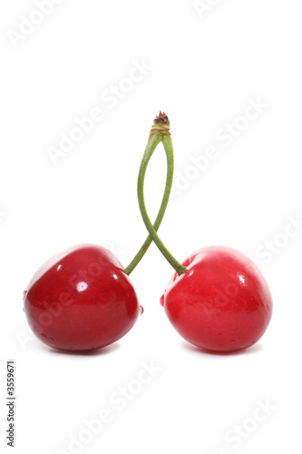 Two cherries joined together over a white background