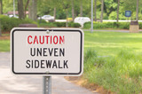 A sign in a park stating Caution Uneven Sidewalk poster