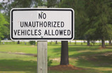 A sign stating No Unauthorized Vehicles Allowed. poster