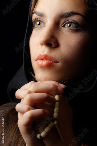 Photo of praying woman in black hood