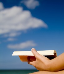 A woman's hand holding a book, on the beach
