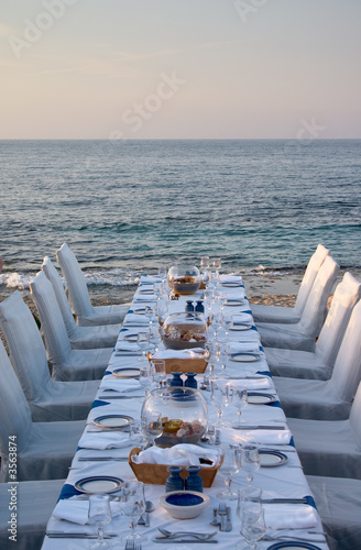 Tuinposter Picknick served table on the sea shore in resort