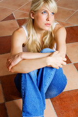 young woman sitting in empty room on mosaic floor