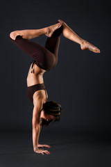 Young female gymnast is stretching her body in a studio