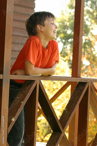 Happy child leaning on the porch balustrade