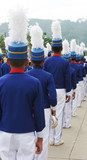 Marching band members in blue and white uniforms poster