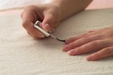 Young female is making french manicure herself. poster