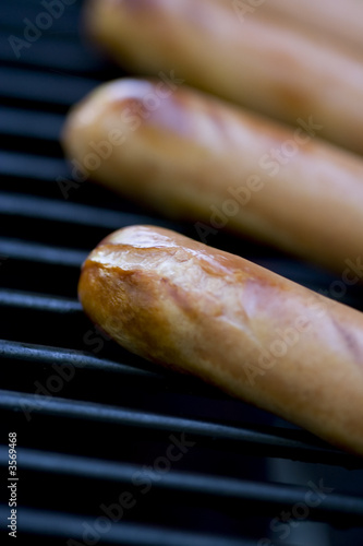 summer bbq  hotdogs on the grill  shallow depth of view