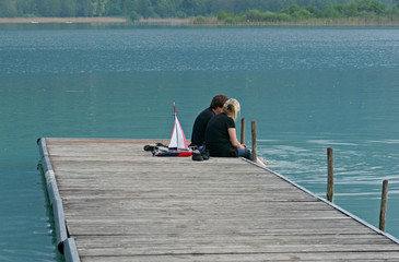 A couple of adults sitting on a pontoon
