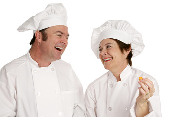 A male and female chef laughing together