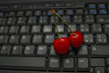 fresh cherry on laptop keyboard