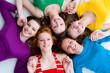 fünf wunderschöne Mädchen liegen am Boden und lächeln