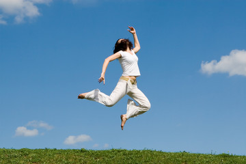 happy young woman is jumping in green grass