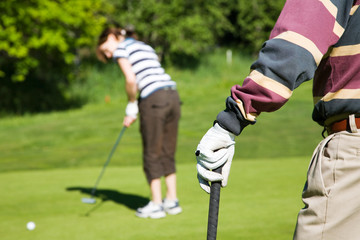 Senior man playing golf with his grandaughter
