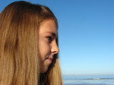 Young girl standing on the beach looking into the distance poster