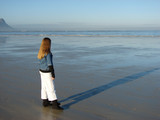 Young girl standing on the beach, looking into the far distance poster