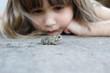 Leinwanddruck Bild - A cute young girl watching a toad
