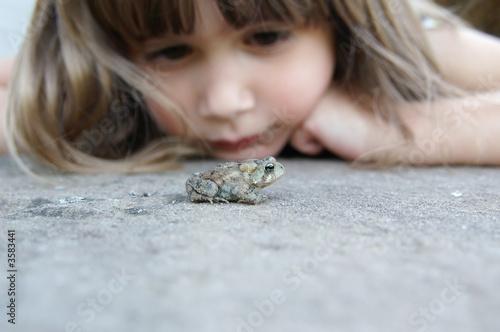 Leinwanddruck Bild A cute young girl watching a toad