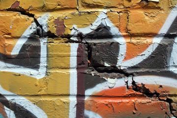 Bright colorful graffiti on a cracked brick wall.