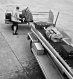 A man is loading luggage onto airplane - B&W version. poster