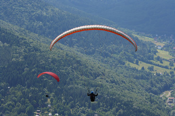 Two gliders against wooded valley