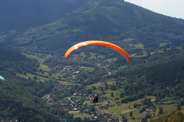 Single glider aginst wooded valley