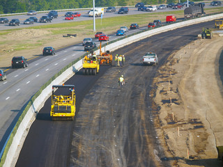 Workers laying asphalt in freeway construction zone