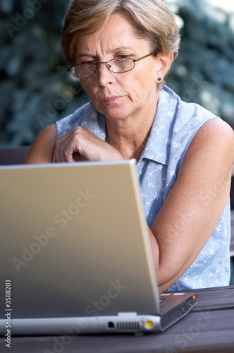 Mid adult woman solving problem on the computer