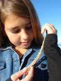 Young girl admiring a string of expensive pearls. poster