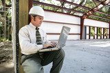 inspector on the construction site with his laptop poster
