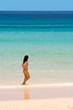 junge frau geht im flachen wasser den strand entlang