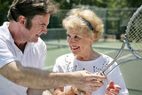 tennis pro gives pointers to older lady poster