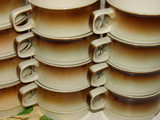 Brown & Beige coloured coffee cups stacked and in rows poster