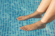 feet refreshing in swimming pool in summer