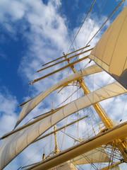 Tall mast with sails on the cloud sky background