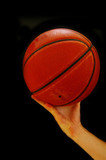 Basketball player reaching with ball in hand, on black poster