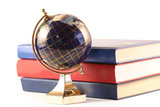 The globe costs near to three books on a white background. poster