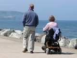 Couple strolling on seaside promenade.  poster
