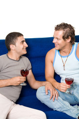 Two homosexual men drinking wine on the sofa