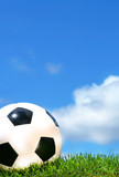 Closeup of a soccerball against a blue sky poster