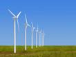 Wind turbines on grass over blue sky
