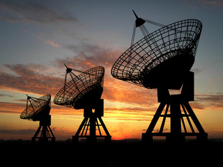 Three satelite dishes over sunset